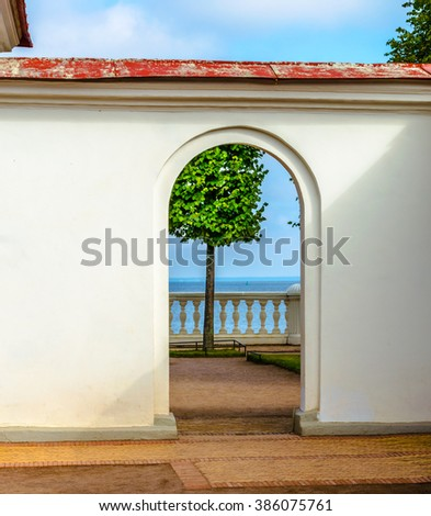 View of a lone tree by the sea through the stone arch - stock photo