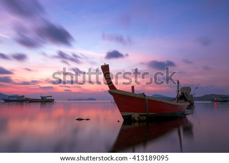 View of a Long Tail Boat Moored in Calm Seas on a Beautiful Tropical Thai Island Beach - stock photo