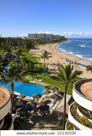 View of a long tropical beach from above (Kaanapali, Maui). Interesting circular buildings in foreground. - stock photo