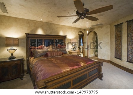 View of a luxury bedroom with silk bedcover on antique bed at home - stock photo