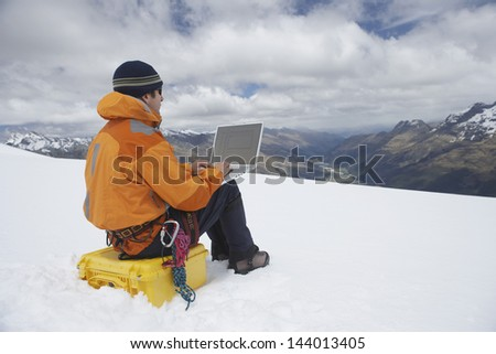View of a male hiker using laptop on snowy mountain landscape - stock photo