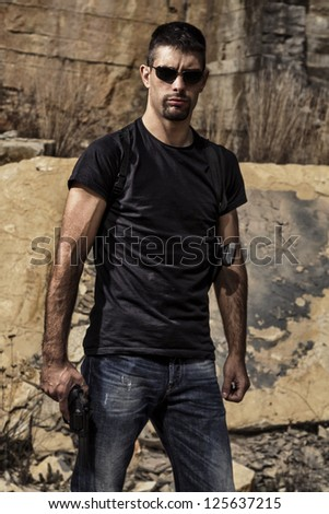 View of a man with a handgun in jeans and black shirt on a stone quarry. - stock photo
