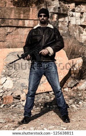 View of a man with a machine gun in jeans and jacket on a stone quarry. - stock photo