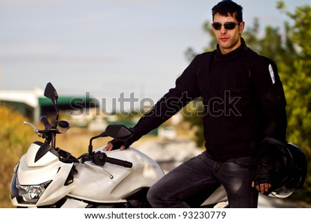 View of a man with a motorcycle on a asphalt road. - stock photo