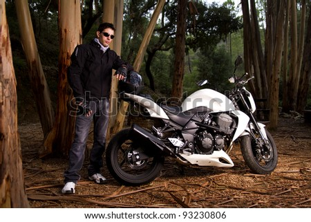 View of a man with a motorcycle on a forest.