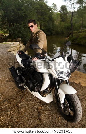 View of a man with a motorcycle on a forest. - stock photo
