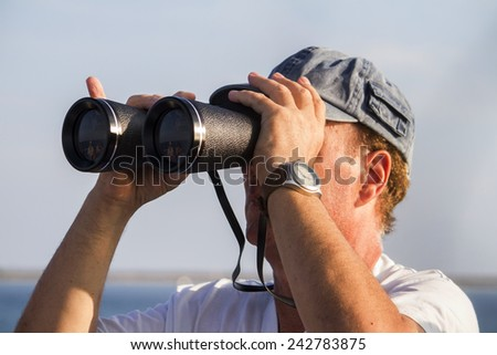 View of a man with binoculars watching the sea horizon.