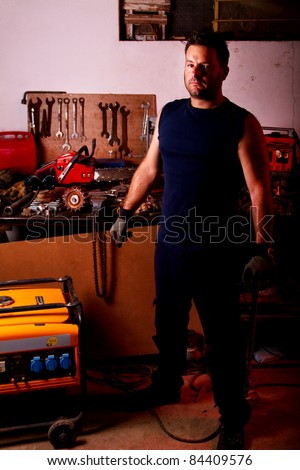 View of a mechanic man inside a garage with many tools. - stock photo