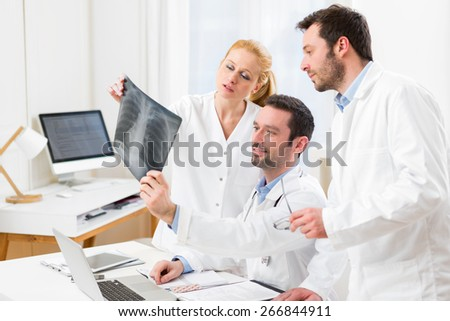 View of a Medical team analysing together a x ray at the hospital