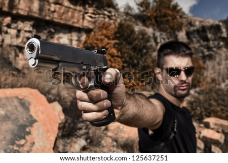 View of a menacing man pointing a handgun in a black shirt and dark shades on a stone quarry.