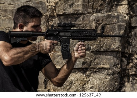 View of a menacing man pointing a machine gun in a black shirt and dark shades on a stone quarry. - stock photo