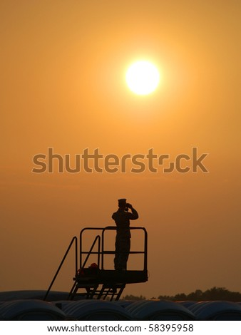 View of a military sentry with binoculars looking off into the distance in front of a low hanging sun.