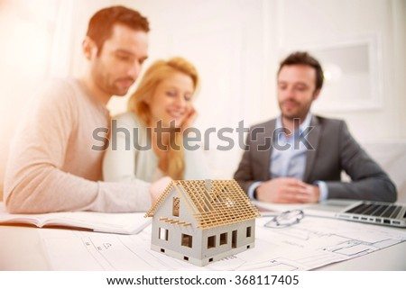 View of a Miniature house in a desk of real estate agent with couple - stock photo