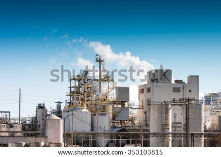 View of a modern day factory, in front of blue sky, with minimum emissions. - stock photo