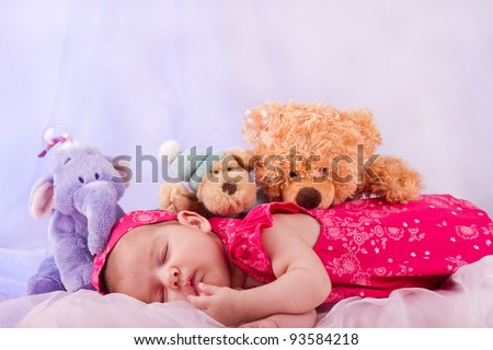 View of a newborn baby on smooth bed with stuffed toy sleeping. - stock photo