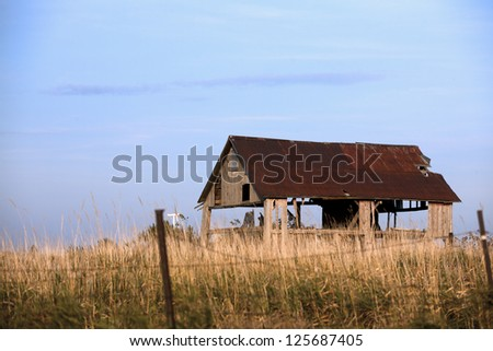 View of a old broken barn with clear sky in the background. - stock photo