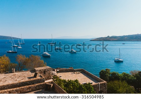 View of a part of Bodrum castle and the boats sailing in Aegean sea - stock photo