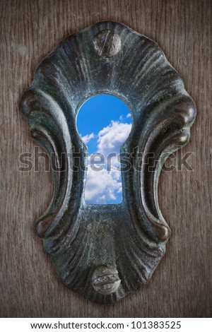 View of a partly cloudy sky through a keyhole - stock photo