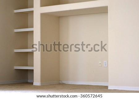 View of a portion of a wall with built in book shelves and cubby in modern apartment.