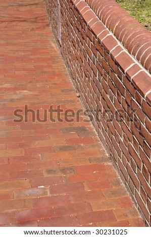 view of a red brick sidewalk and low wall