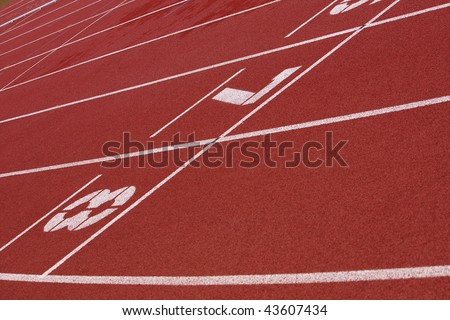 View of a red tartan athletic running track with white numbers.