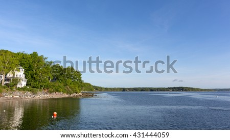 View of a rocky coastline and rippling water at Northport, Maine in the late springtime. - stock photo