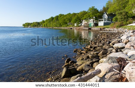 View of a rocky coastline in the foreground with small vacation cottages in the background at Northport, Maine in the early morning light. - stock photo
