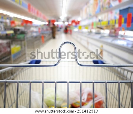view of a shopping cart with grocery items at supermarket  blurred background - stock photo