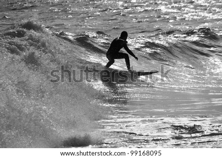 View of a silhouette of a boy surfin' the waves. - stock photo