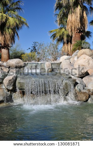 View of a small waterfall at a park in Palm Desert, California. - stock photo