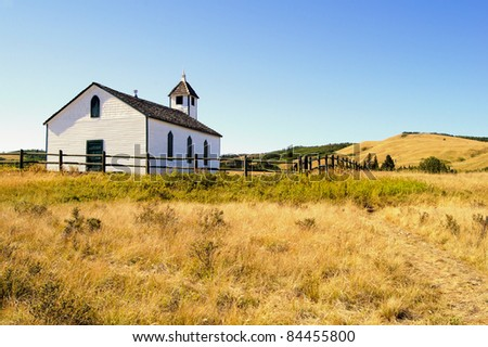 View of a small wooden pioneer church in the prairies during autumn - stock photo