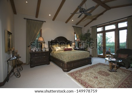 View of a spacious bedroom with beamed ceiling and patio doors - stock photo