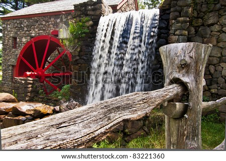 View of a split rail fence with a grist mill and waterfall in the background - stock photo