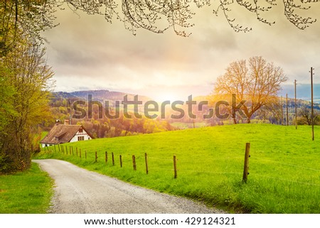 View of a spring day in the Switzerland, rural landscape at sunrise -  Switzerland rural sunset landscape. Countryside farm, green field, sun light and cloud. Europe. - stock photo