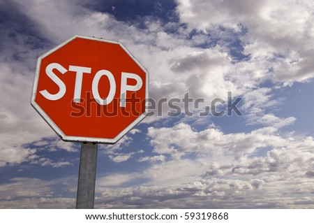 view of a stop signal with cloudy sky - stock photo