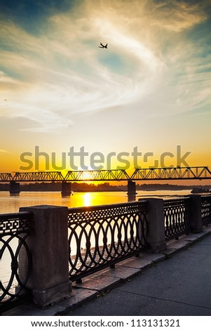 view of a sunset and the flying plane from the river embankment - stock photo