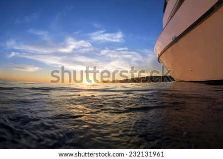 View of a sunset from the surface of the ocean shows a boat facing the beautiful horizon while nighttime ensures.  - stock photo