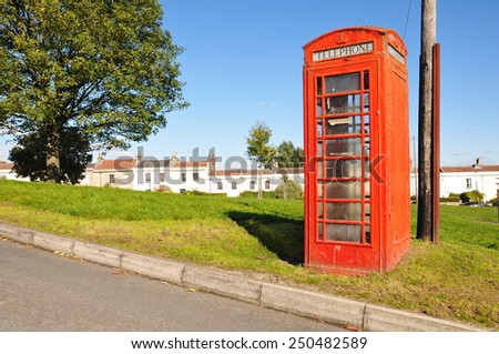 View of a Traditional British Red Phone Box on a Country Road - stock photo