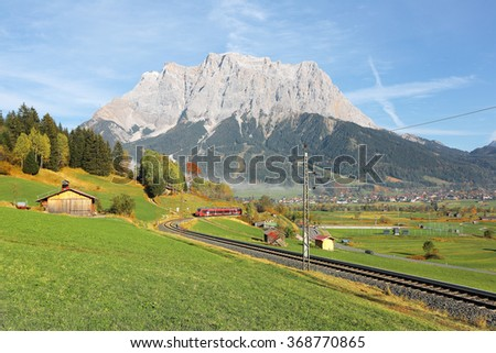 View of a train traveling through green fields with rugged Zugspitze Mountain in background on a beautiful sunny day in Lermoos, Tirol, Austria ~ Brisk autumn scenery of idyllic Tyrolean countryside  - stock photo