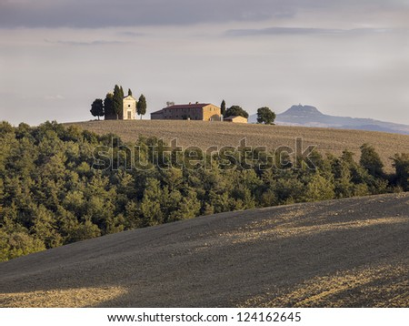 View of a Tuscan field with barn in the background. - stock photo