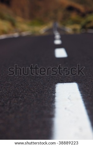 View of a two lane highway from a low angle with shallow depth of field. - stock photo