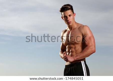 View of a very fit male model with muscles.Fashion photo.Wide angle. - stock photo