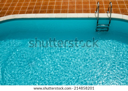 View of a vivid blue swimming pool with stairs. - stock photo