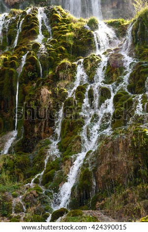 View of a waterfall, flowing from high inside meadow area, with green trees and plants around. - stock photo