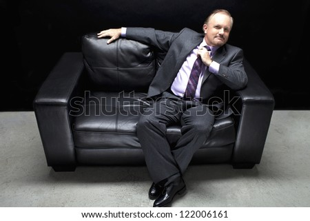View of a well dressed mafia sitting on black couch. Model: Dan Sanderson