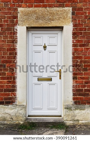 View of a White Front Door of a Red Brick English Town House - stock photo