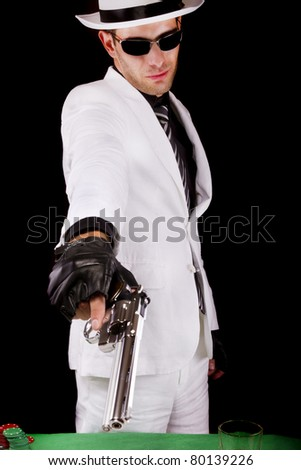 View of a white suit gangster man holding a gun. - stock photo