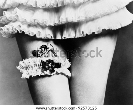 View of a woman hiding a tattoo with a garter on her thighs