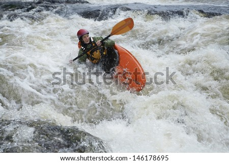 View of a woman kayaking in rough river - stock photo