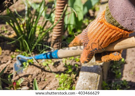 view of a woman's hand hoeing weeds in the garden on a hot summer day, weeding grass, garden and cleaning work in the garden in the spring soil preparation